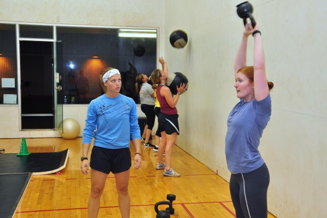 Capt. Emily Hannenberg (left), Engineer Staff Officer with the 84th Eng. Bn., leads 2nd Lt. Diana Worth (right) in a CrossFit exercise September 9 2011. The program was developed to bring fun, free and effective workout regimen to Soldiers and Spouses of the Never Daunted battalion.