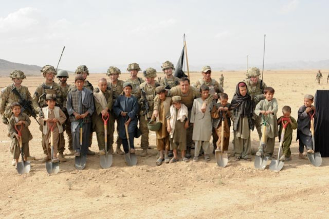Soldiers in 2nd Battalion, 87th Infantry Regiment, stand with local schoolchildren on the site of the new Kandalay School and clinic, Oct. 10.