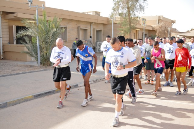 Lt. Gen. Frank G. Helmick, deputy commanding general for operations, United States Forces-Iraq, and Command Sgt. Maj. Earl L. Rice, his senior enlisted advisor, set their watches as the prepare for a five kilometer run with with members of the Iraqi men's mid-to-long distance Olympic running team at Al Asad Air Base, Iraq, Oct. 23, 2011. American service members got the chance to train and run with the Olympians during a goodwill visit.