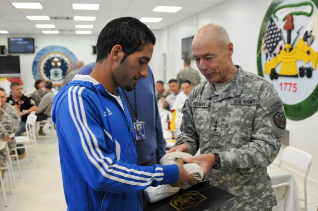 Lt. Gen. Frank G. Helmick, deputy commanding general for operations, United States Forces-Iraq, presents paratrooper gifts to members of the Iraqi men's mid-to-long distance Olympic running team enjoy lunch after a run with American service members at Al Asad Air Base, Iraq, Oct. 23, 2011. American service members got the chance to train and run with the Olympians during a goodwill visit.
