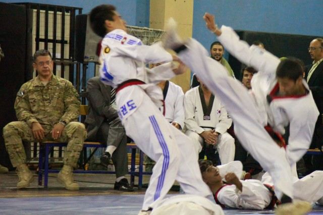 """KABUL, AFGHANISTAN """" U.S. Navy Rear Adm. Hal Pittman, far left, of Tampa, Fla., watches a dramatization by the Afghanistan National Taekwondo Federation Junior Team at the International Security Assistance Force Headquarters gym, Oct. 22. The team of 6 Afghan girls and 11 Afghan boys demonstrated their athletic abilities to kick, break boards and work as a team, and the ISAF crowd loved it. Through the Youth and Sports Outreach program, ISAF is working with the Afghan's to reach 68 percent of the Afghan population who are below the age of 30. Sports programs are a healthy alternative to youth, who may be at risk of being influenced by drug use or enemy insurgents."""