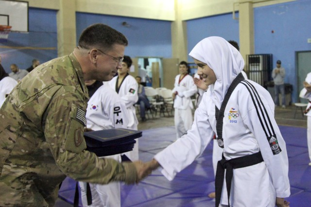 """KABUL, AFGHANISTAN """"U.S. Navy Rear Adm. Hal Pittman, left, of Tampa, Fla., shakes the hand of an Afghan girl following a demonstration by the Afghanistan National Taekwondo Federation Junior Team at the International Security Assistance Force Headquarters gym, Oct. 22. The team of 6 Afghan girls and 11 Afghan boys demonstrated their athletic abilities to kick, break boards and work as a team, and the ISAF crowd loved it. Through the Youth and Sports Outreach program, ISAF is working with the Afghan's to reach 68 percent of the Afghan population who are below the age of 30."""