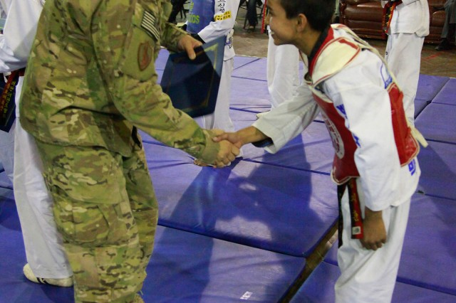 """KABUL, AFGHANISTAN """"U.S. Navy Rear Adm. Hal Pittman, left, of Tampa, Fla., shakes hands with Sajad Sohrabzada following a demonstration by the Afghanistan National Taekwondo Federation Junior Team at the International Security Assistance Force Headquarters gym, Oct. 22. The team of 6 Afghan girls and 11 Afghan boys demonstrated their athletic abilities to kick, break boards and work as a team, and the ISAF crowd loved it. Through the Youth and Sports Outreach program, ISAF is working with the Afghan's to reach 68 percent of the Afghan population who are below the age of 30."""