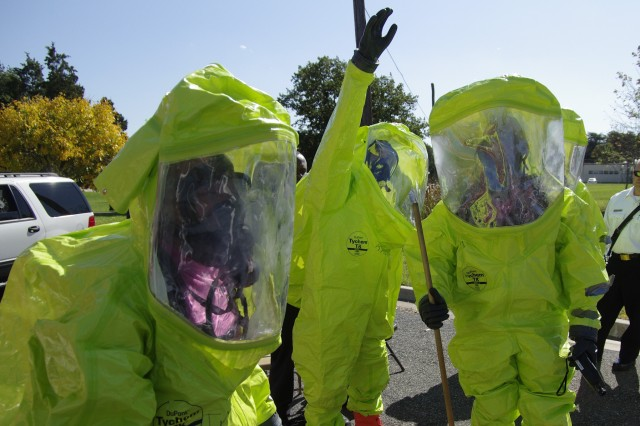 """During one demonstration, firefighters suit up in HAZMAT gear before handling a """"suspicious"""" package found beneath the tire of a car."""