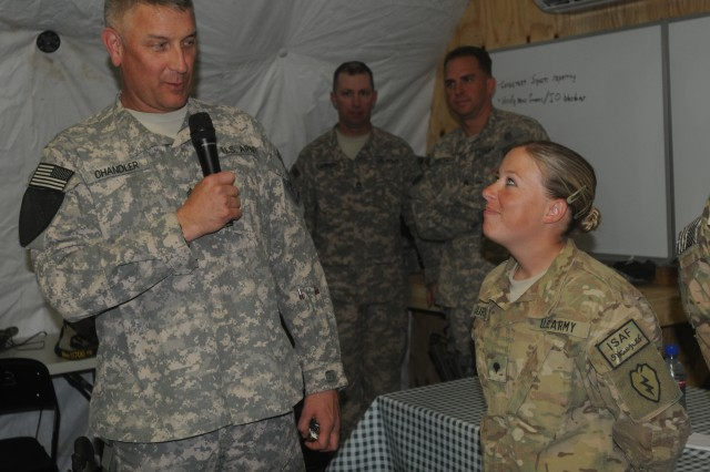 Spc. Nicole Jurecko, with the 1st Stryker Brigade Combat Team, 25th Infantry Division, asks questions about where the Army is going, then listens to Sgt. Maj. of the Army Raymond F. Chandler III respond during his visit to Forward Operating Base Masum Ghar, Afghanistan, Oct. 20, 2011.
