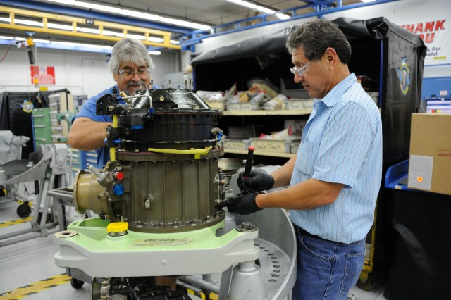 Aircraft Part Mechanics, Fernando Caballero and Richard Franco, remove subassemblies form a Navy UH-1N Huey Transmission. Photo by Jaclyn Nix