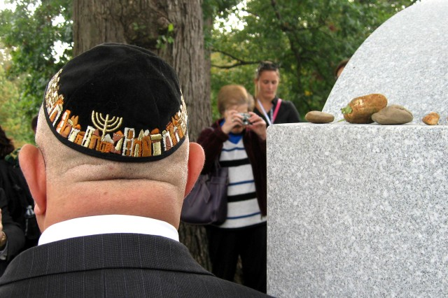 A Jewish war veteran stands next to the Jewish Chaplains Memorial following dedication ceremonies at Arlington National Cemetery in Arlington, Va., Oct. 24, 2011. The rocks on the memorial follow the traditional Jewish practice of placing a rock on the headstone.