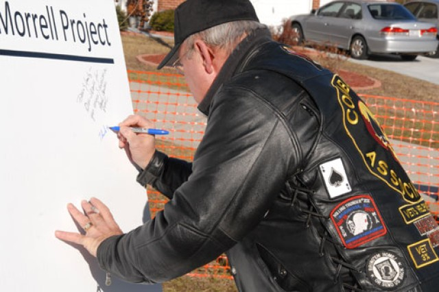 A member of the community signs a poster commemorating Morrell's new addition and thanking him for his service and sacrifice.