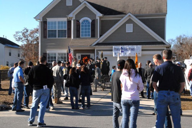 Community volunteers and well wishers gather in front of the Morrell home before the groundbreaking ceremony Jan. 29.