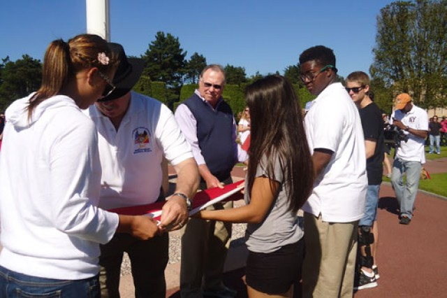 Amanda Hoskins helps other students fold the American flag at the Normandy American Cemetery, during their June visit to France as part of the National History Day program.