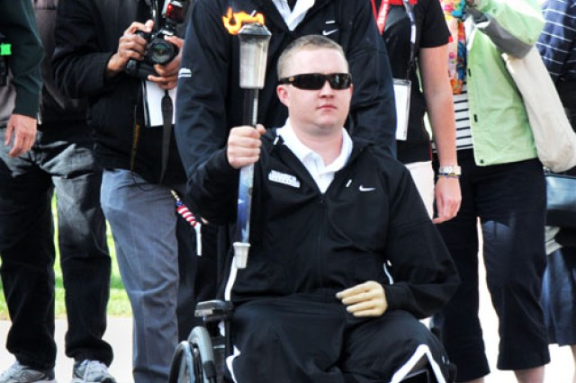 Army team torch-bearer Pfc. Joshua Bullis, who competed in standing and prone rifle events, leads the team down the Olympic boulevard during opening ceremonies for the 2011 Warrior Games in Colorado Springs, Colo.