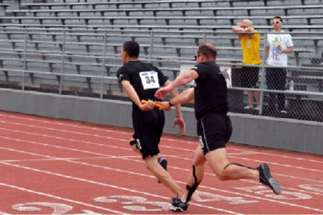 Robert Laux hands off the baton to teammate Robbie Gaupp during the last leg of the 400-meter relay at the 2011 Warrior Games.