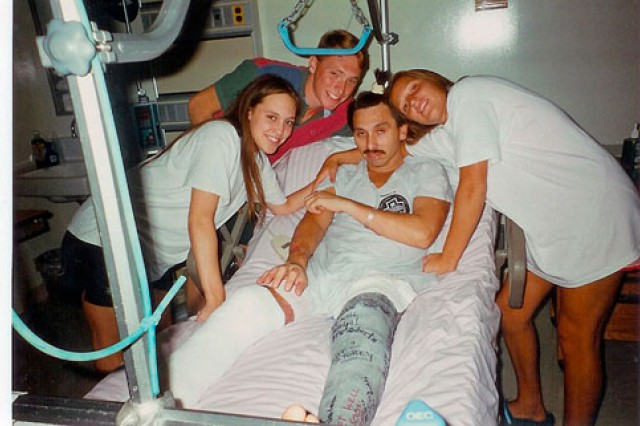 Now-retired Chief Warrant Officer 4 Dan Laguna recovers in the Fort Campbell, Ky., hospital after a horrific helicopter crash. He is pictured with his daughters Michelle and Jamie and son Chris, who was also in special operations and given leave to help care for his father.