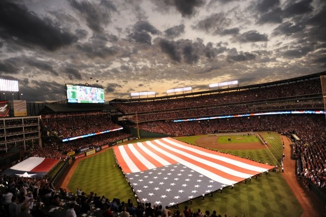 Members of the Texas Military Forces participate in Game 3 of the Major League Baseball World Series in Arlington, Texas, Oct. 22, 2011, by assisting in the unfurling of the United States flag. Service members from the Army, Navy, Air Force and Marines also assist in this pregame tradition.