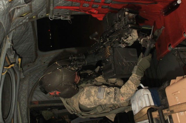 Sgt. Joe Loscheider, a flight engineer with B Company, 2-211th General Support Aviation Battalion, prepares to move his M240B machine gun into position prior to heading out on a mission from Camp Taji, Iraq, the night of Oct. 7, 2011.