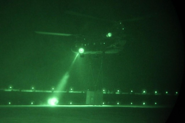 A CH-47 Chinook prepared to lift a container of equipment off the ground while out on mission in Iraq on the night of Oct. 6, 2011.