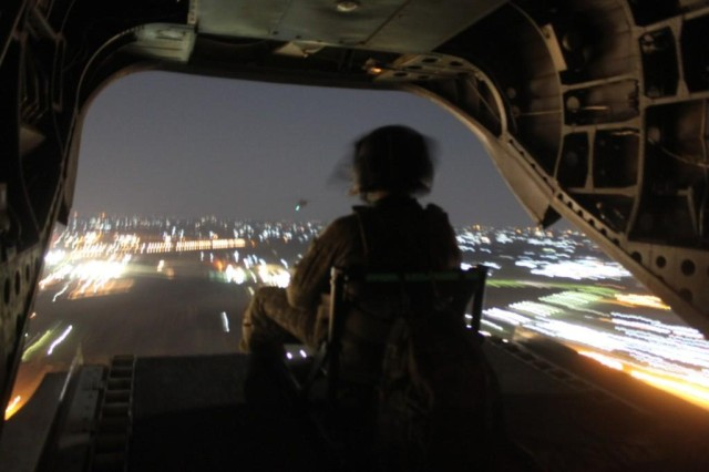 A flight engineer, with B Company, 2-211th General Support Aviation Battalion, keeps a vigilant eye out for trouble while flying a mission in Iraq the night of Oct. 6, 2011.
