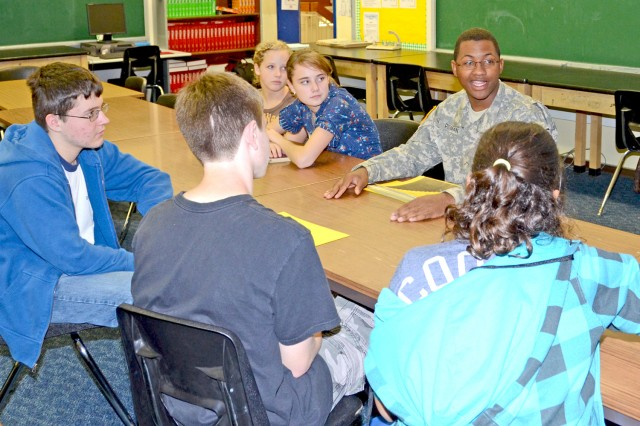 Pvt. 2 Quinton Pittman, V Corps, leads a group of Wiesbaden Middle School students in a discussion about ways to prevent bullying during Students Against Violence and Victimization of Youths Commitment Day Oct. 13.