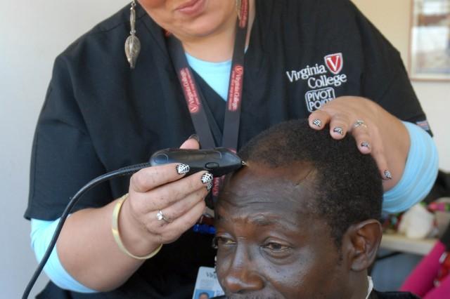 Virginia College student Karen Maloney gives a free haircut to veteran Eddie Robins.