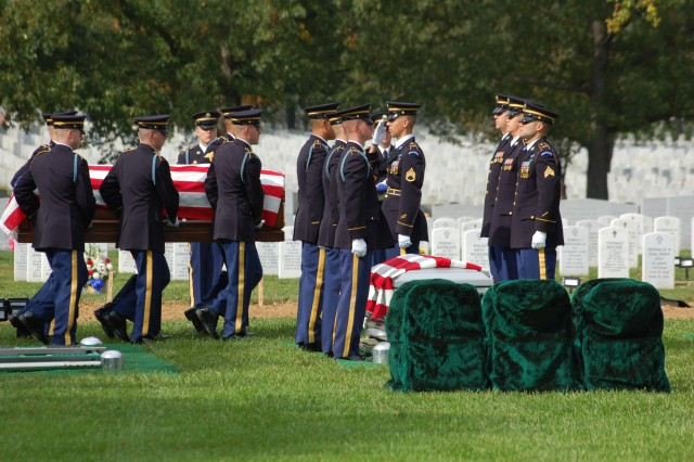 Members of the casket team carry caskets into Section 60 of Arlington National Cemetery, Va., for the burial service of 10 Army Airmen from World War II Oct. 26, 2011.