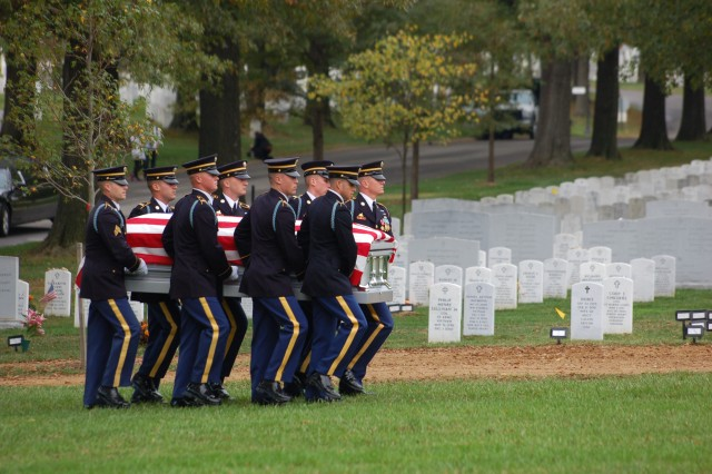 Members of the casket team carry remains into Section 60 of Arlington National Cemetery, Va., for the burial service of 10 Army Airmen from World War II Oct. 26, 2011.