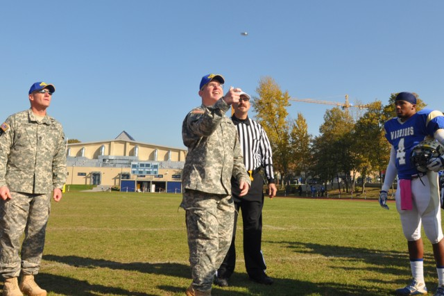 Brig. Gen. Ricky Gibbs, V Corps commander, flips the coin to determine which team chooses possession first at a varsity football game between Wiesbaden High School and Lakenheath (England) High School, Oct. 22, in Wiesbaden.