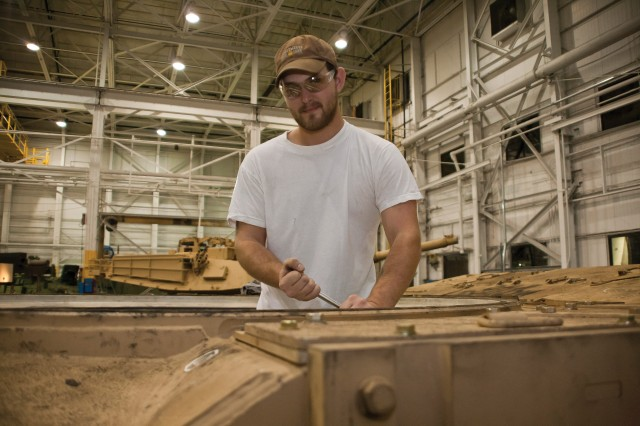 Doug Rose removes components from the interior of a turret at Anniston Army Depot.