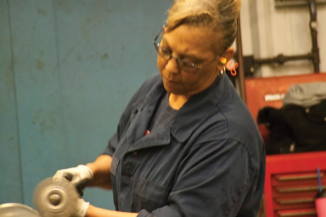 Sheila Green prepares a gun tube for painting and finishing at Anniston Army Depot.