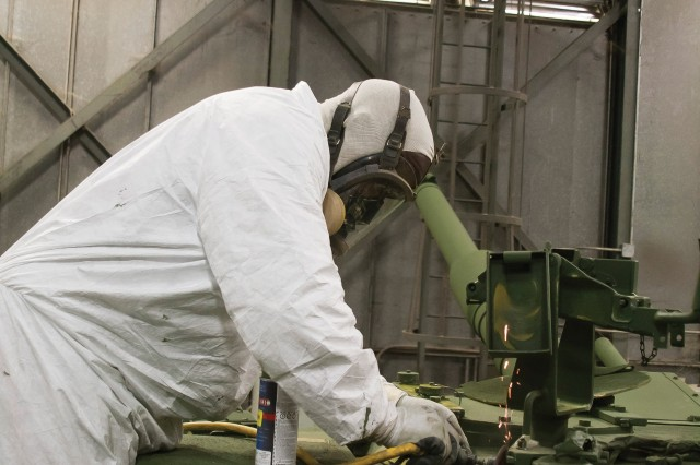 Chris Evans touches up the paint on a M1 Abrams Tank in Anniston Army Depot's Cleaning, Finishing and Painting Division.