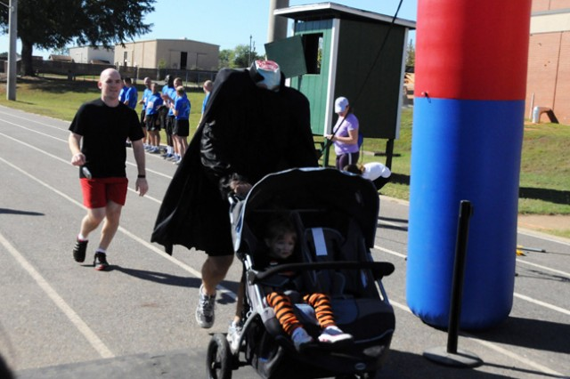 First Lt. Matthew Cox, B Co., 1st Bn., 145th Avn. Regt., pushes his daughter across the finish line during the fun run portion of the Spooky 5K last year. Cox dressed as the Headless Horseman from The Legend of Sleepy Hollow, but didn't participate in the costume contest.
