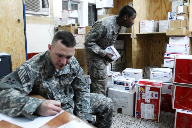FORWARD OPERATING BASE FALCON, Iraq -- Sgt. Charles Kowalski makes a list of mail recipients to post outside the Headquarters Mail Room Dec. 10, 2008, at Forward Operating Base Falcon, Iraq, while Sgt. Frederick Gregory sorts mail.
