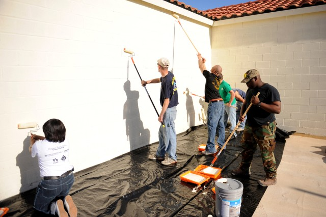 Soldiers and spouses from 2-5 Cav. Regt., 1st Cav. Div. take part in Make a Difference Day Oct. 21 by painting the walls of the Armed Services YMCA in Harker Heights. The Armed Services YMCA is the unit's battalion partner.(U.S. Army photo by Daniel Cernero, III Corps and Fort Hood Public Affairs)