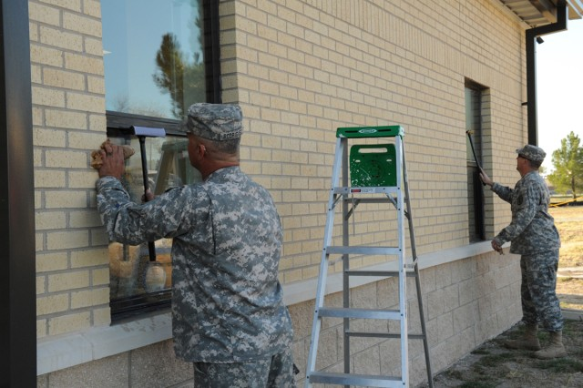 Sergeant Carlos Rodriguez and Sgt. 1st Class Chris Switzer, both assigned to the Warrior Transition Brigade, clean windows at the Soldier and Family Assistance Center Oct. 21. The WTB Soldiers took part in the morning events for Make a Difference Day. (U.S. Army photo by Rachel Parks, III Corps and Fort Hood Public Affairs)
