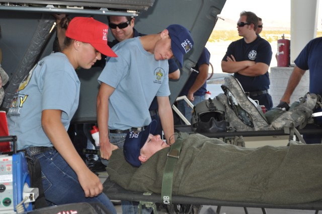 Fire explorers Cheyenne Tacy and Brandon Browne lift a simulated casualty onto a helicopter during the Inland Empire Fire Explorers Academy Oct. 21 at Fort Irwin.