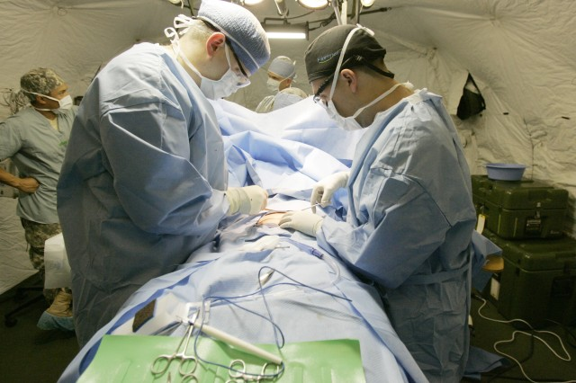 Capt. Nathan Zwintscher, left, and Capt. Jacob Swann operate on Staff Sgt. Matthew Horton inside a mobile field surgery operating room Oct. 19, 2011, at Joint Base Lewis-McChord, Wash. .