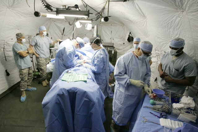 Capt. Nathan Zwintscher, left, and Capt. Jacob Swann operate on Staff Sgt. Matthew Horton inside a mobile field surgery operating room Oct. 19, 2011, at Joint Base Lewis-McChord, Wash.