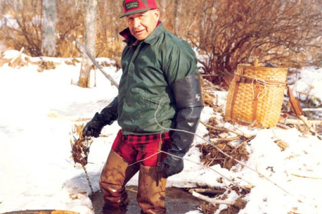 Harry Thompson, who was inducted into the New Hampshire Trappers Association Hall of Fame, checks an under-ice trap in the snowy foothills of the White Mountains.