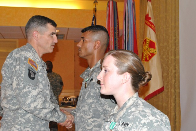 Joint Force Headquarters-National Capital Region and Military District of Washington Commander Maj. Gen. Michael S. Linnington congratulates Staff Sgt. Michael Williams [background] and Spc. Sarah Deckert [foreground] on their respective NCO and Soldier of the Year awards presented Oct. 20.