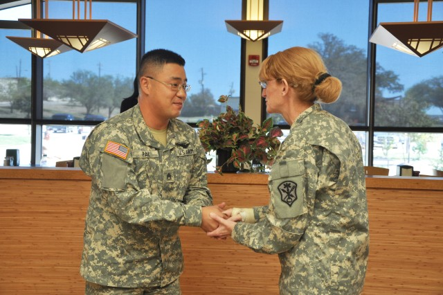 Maj. Gen. Mary Legere, commander of Intelligence and Security Command, shakes hands with Staff Sgt. Hwon Pak, the command's Language Professional of the Year. Legere handed her commander's coin to Pak following a luncheon with him and other Soldiers of the 717th Military Intelligence Battalion at the Lackland Air Force Base Annex Oct. 19. (U.S. Army photo by Gregory Ripps)