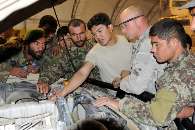 Staff Sgt. Mark Lason (second from right), shop foreman in Company F, 2nd Battalion, 87th Infantry Regiment, teaches Afghan National Army Soldiers and Afghan National Police mechanics how to perform basic maintenance on a military vehicle, at Forward Operating Base Pasab, Afghanistan, Oct. 18, 2011.
