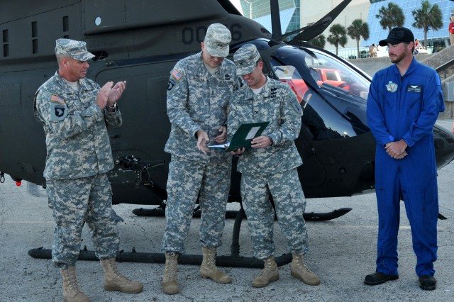 Col. John Morgan, 1st Combat Aviation Brigade commander, shows off his new OH-58D logbook to Maj. Gen. James E. Rogers, Commanding General, Aviation and Missile Command for the newly repaired OH-58D Kiowa Warrior from Corpus Christi Army Depot. Looking on is Col. Christopher B. Carlile, CCAD Commander and Douglas Brubaker, CCAD OH-58D Crew Chief. US Army photo by Ervey Martinez (RELEASED).