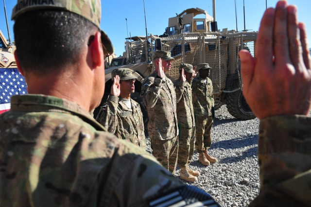 Col. Lawrence Kominiak, foreground, the Task Force Resolute commander, issues the Oath of Enlistment to five Soldiers during a mass reenlistment ceremony at the Headquarters and Headquarters Company, Special Troops Battalion, TF-Resolute motorpool at Kandahar Airfield Oct. 24. (U.S. Army photo by Staff Sgt. Alexander Burnett)