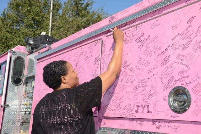 "Chrishawn Turner, breast cancer survivor and retired Army veteran, adds her name to one of the ""Pink Heals"" fire trucks parked in front of Carl R. Darnall Army Medical Center Oct. 25. The trucks made their first appearance at Fort Hood as part of the national Pink Heals Tour""a nonprofit group of firefighters and other volunteers who drive the pink trucks around the country for two months to raise awareness for the fight against breast cancer.  (U.S. Army photo by Patricia Deal, CRDAMC Public Affairs)"