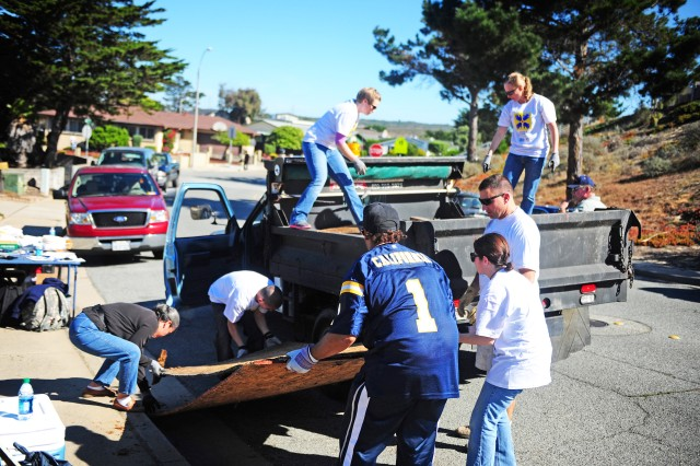 PRESIDIO OF MONTEREY, Calif. - Volunteers in Seaside load trash onto a truck to help clear a local World War II veteran's house of debris during Make A Difference Day.