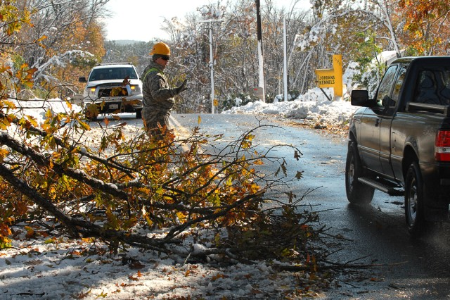 Spc. Seth Tuper, a combat engineer, 379th Engineer Company, 101st Engineer Battalion, Massachusetts Army National Guard, directs traffic around a tree that had fallen on Springfield Street in Wilbraham, Mass., blocking half the road and creating a potential traffic hazard on Oct. 30, 2011. As Tuper directed traffic, other Soldiers from his unit used chain saws to quickly cut down the tree.