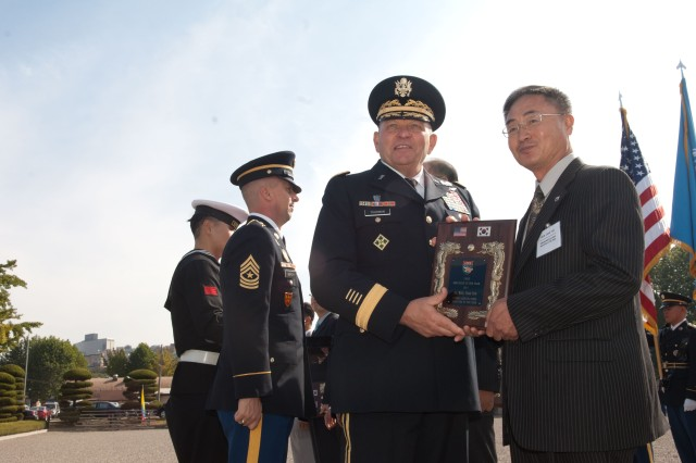 Gen. James Thurman, the United States Forces Korea commanding general, presents the Civilian Employee of the Year Award in the Korean Service Corps to Won Chae-yon during a ceremony on Knight Field Oct. 20. The 19 winners were recognized for their help keeping the U.S. and ROK militaries running strong.