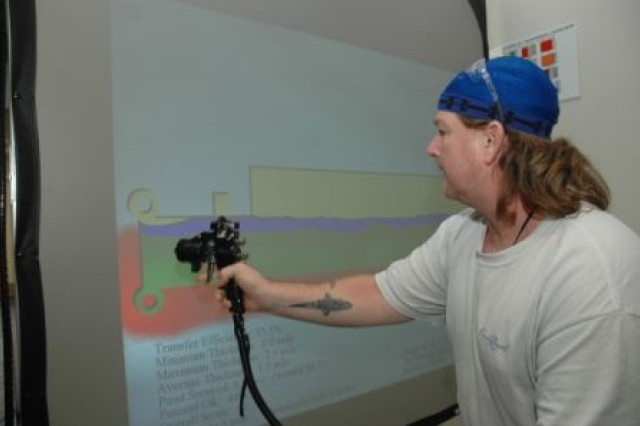 Mike Holley demonstrates the Virtual Reality Paint Simulator. Photo by Jaclyn Nix