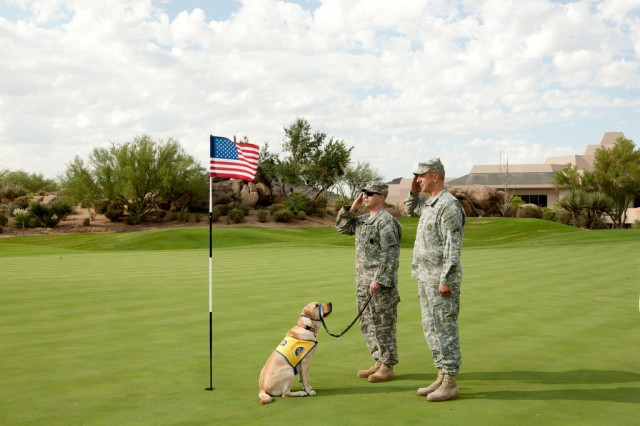 Puppy Clint II observes Staff Sgt. Bryan Thompson and Sgt. 1st Class Michael LaHaye, Scottsdale Recruiting Station, salute the American Flag on  the 18th green during a golf tournament that benefits Canine Companions for Independence at the Troon North Golf Club in Scottsdale, Ariz., Sept. 9.