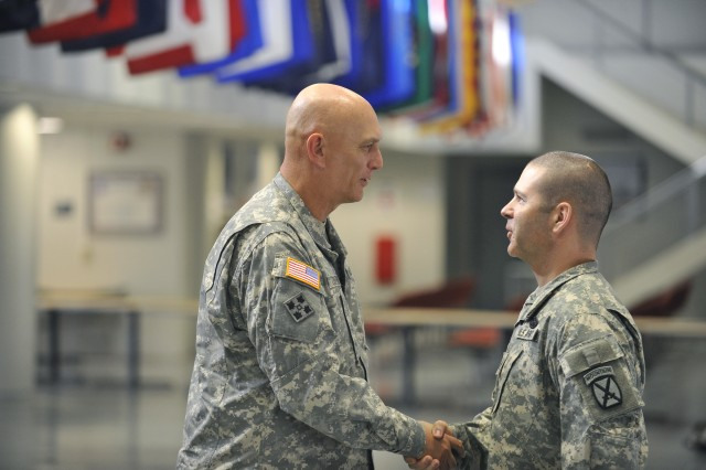 U.S. Army Staff Sgt. Christopher McCuiston, from the 10th Mountain Division, shakes hands with  Gen. Raymond T. Odierno, Chief of Staff of the Army, during a reenlistment ceremony hosted by Odierno at Fort Drum, N.Y. Oct. 25, 2011.