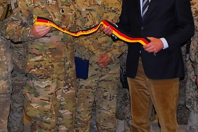 CAMP MARMAL, Afghanistan -- Lt. Col. Michael Burns (left), a native of New Brockton, Ala., holds a streamer awarded to the 1st ACB with President Christian Wulff of Germany (right) Oct. 17. Wulff talked with key leaders and soldiers during a surprise visit of coalition base Camp Marmal and honored the1st ACB with this streamer. (U.S. Army photo by Sgt. Richard Wrigley, 1st ACB, 1st Cav. Division Public Affairs)